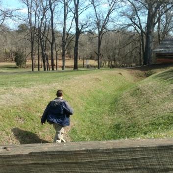 Dr. Ferro walking through a trench